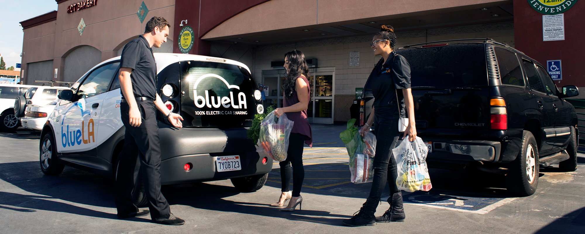 BlueLA car driver helping a passenger with groceries