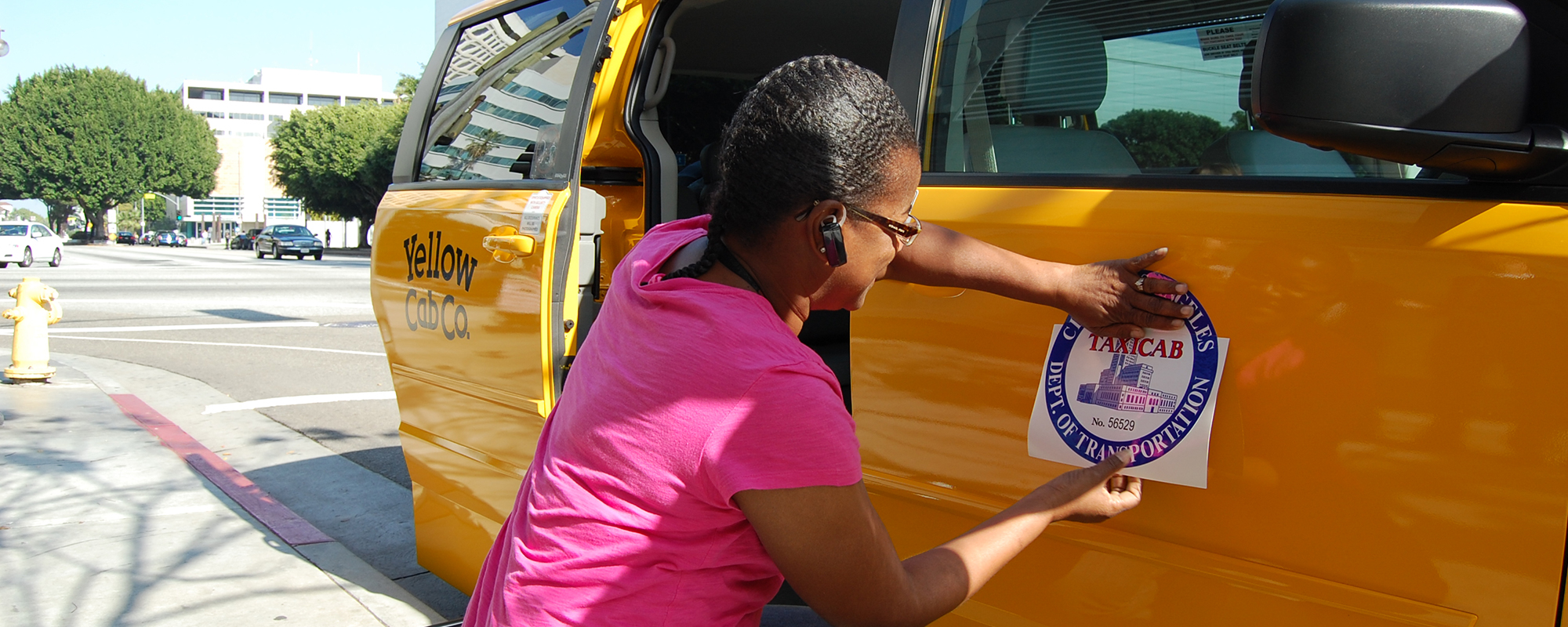 woman placing a taxi label on a yellow cab