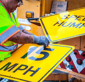 worker with a speed hump sign
