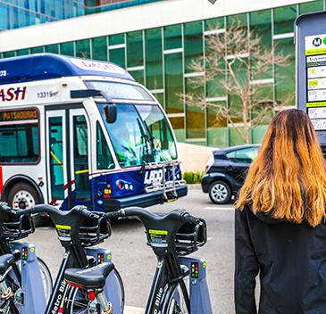 woman at a Metro Bike kiosk, Dash bus in the background